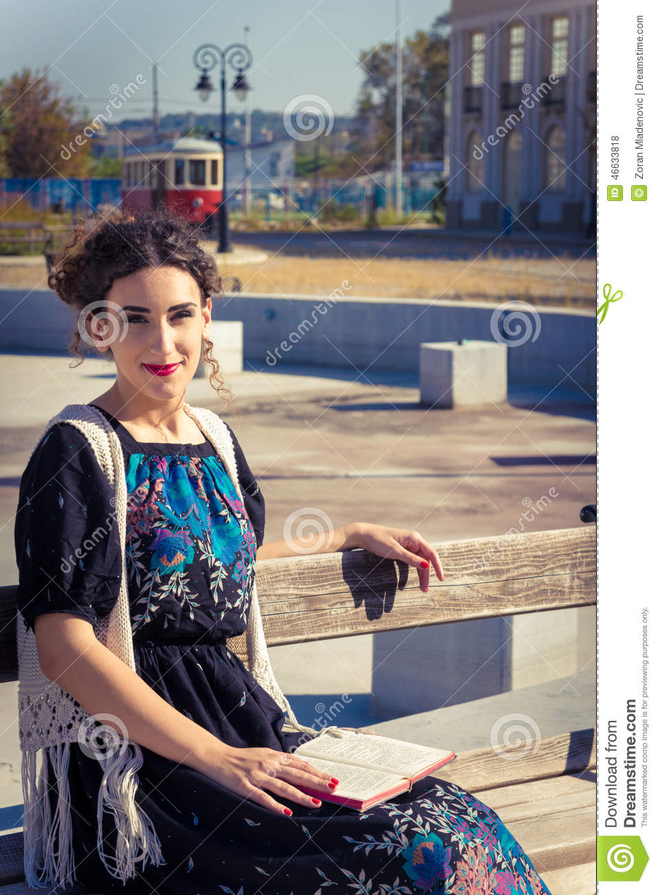 Woman sitting on a bench in the old town and reading a book