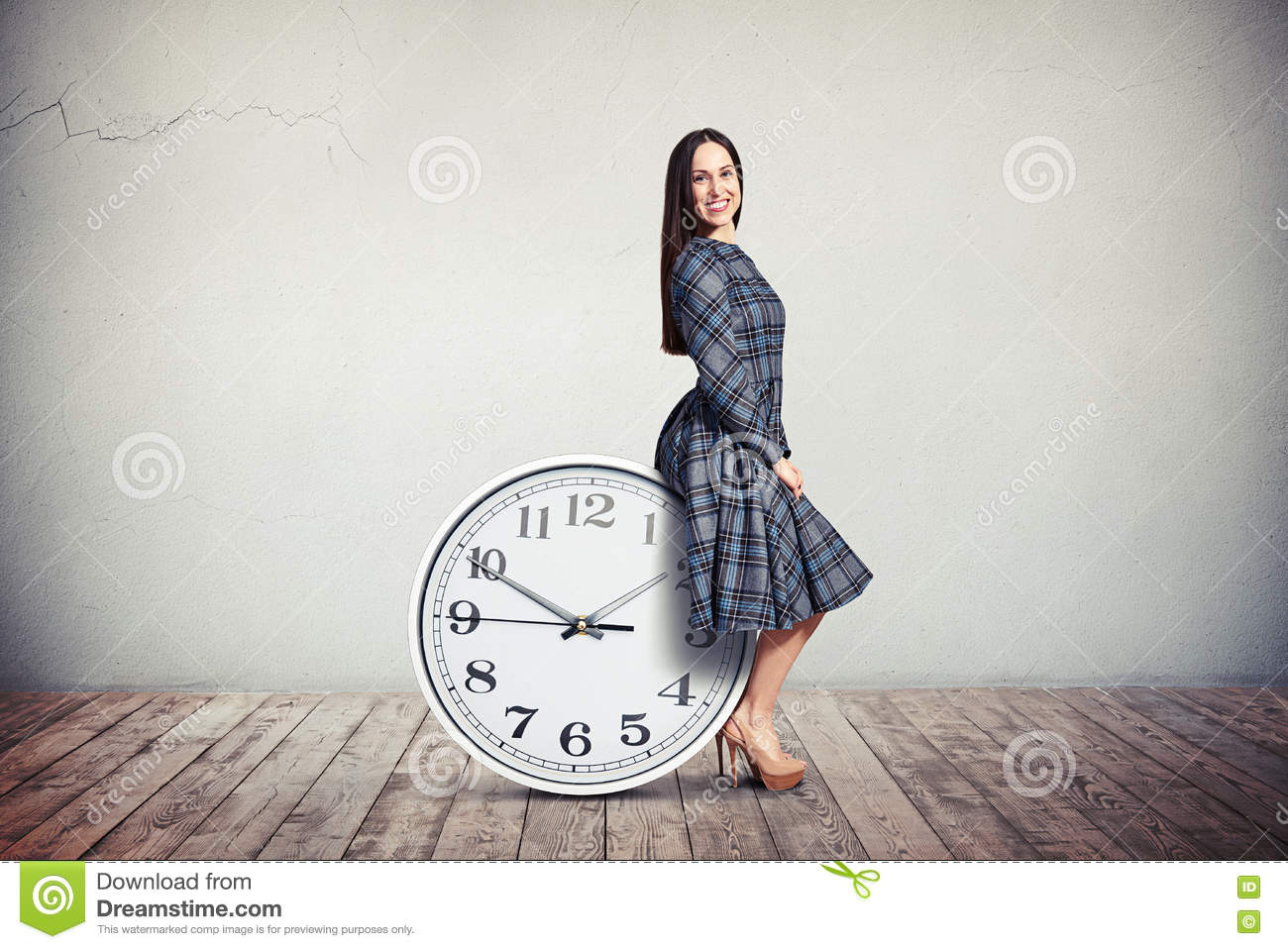 A woman is sitting on the big clock