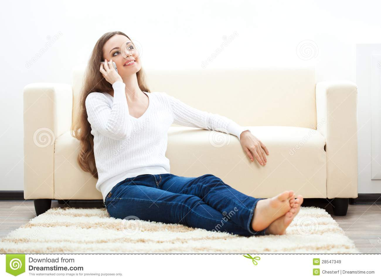 Woman Sitting On Carpet And Talking By Phone Royalty Free