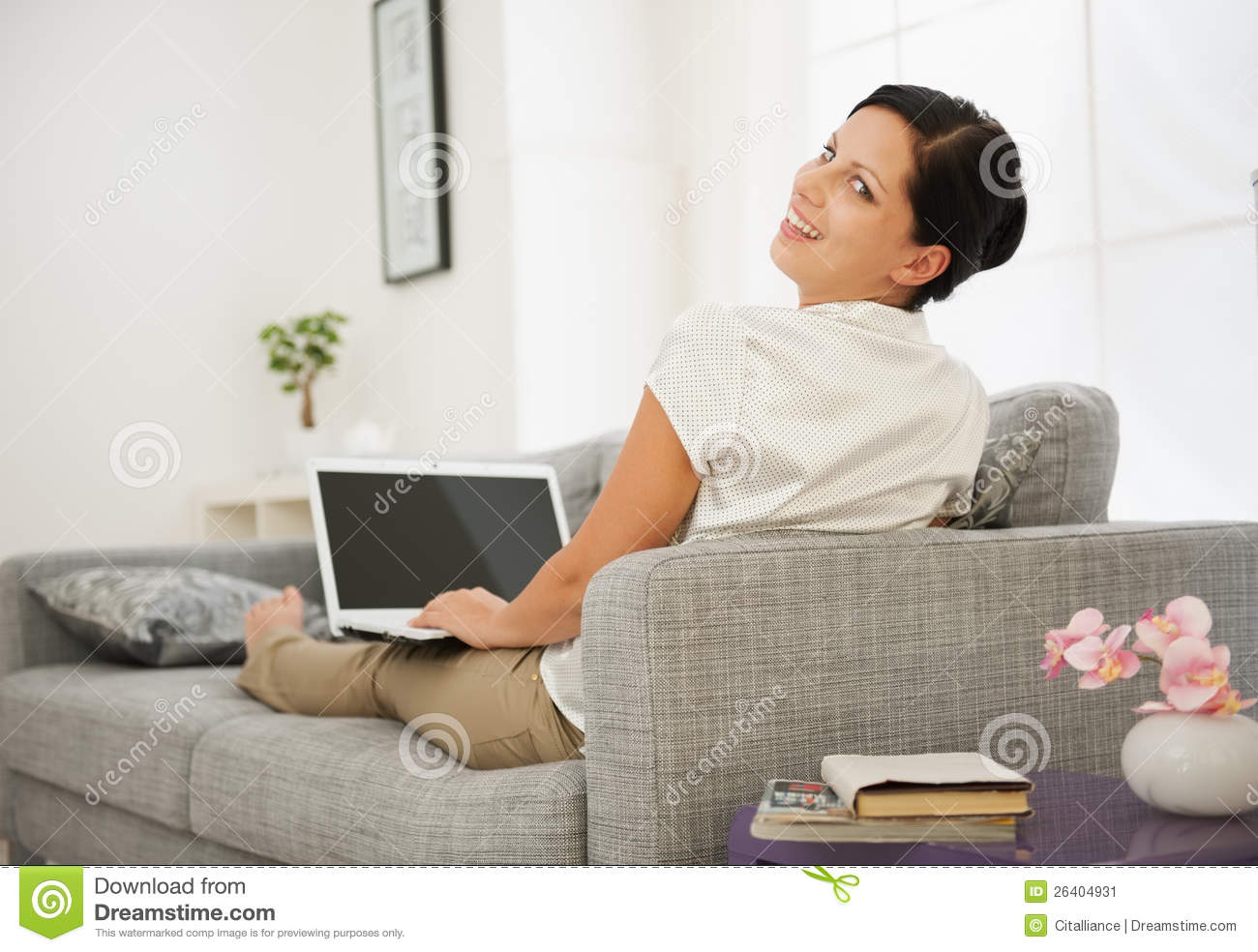 woman sitting on couch and working on laptop stock image. Black Bedroom Furniture Sets. Home Design Ideas