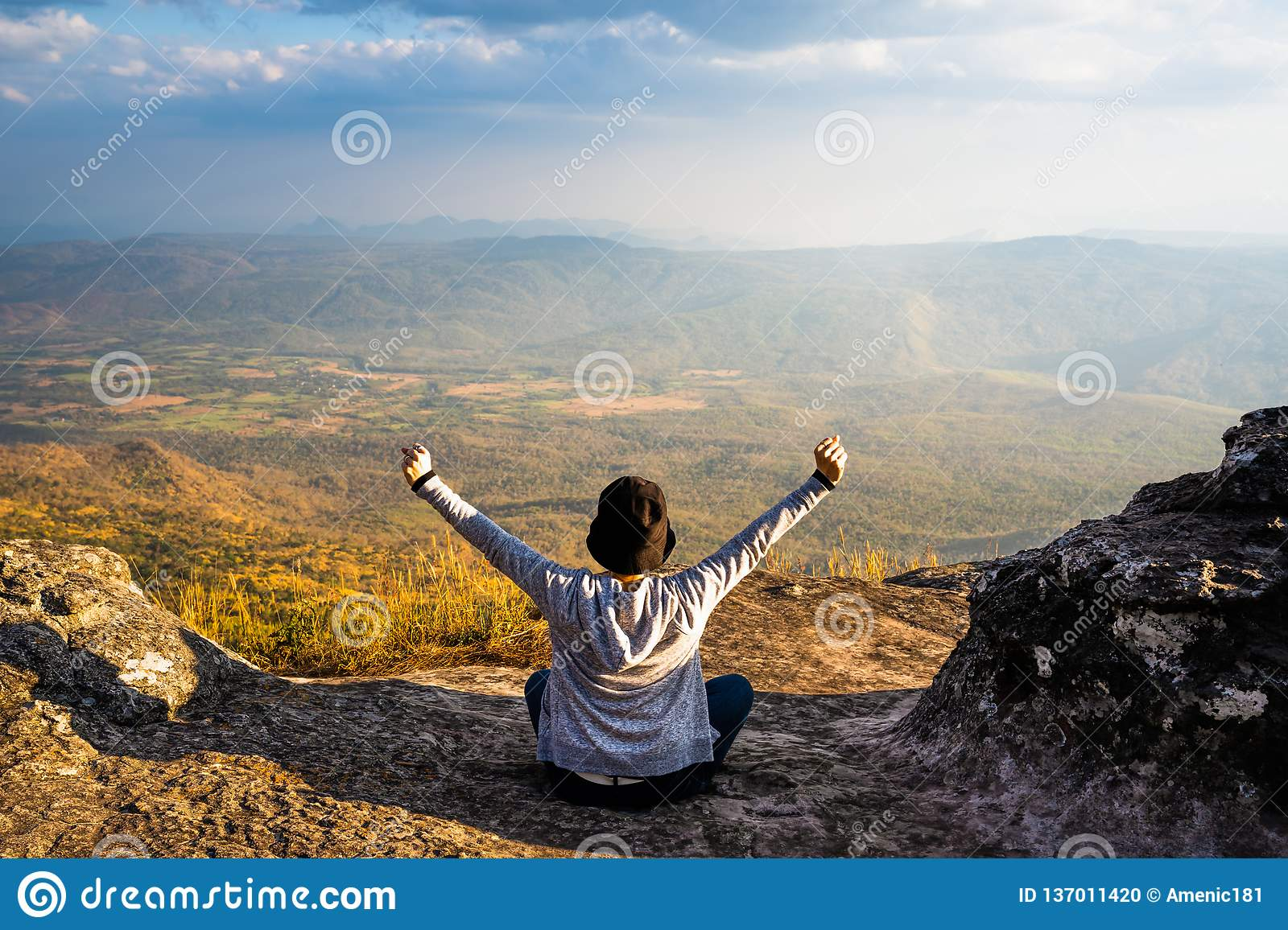 A woman sitting down with hands up on rocky mountain looking out at scenic natural view and beautiful blue sky