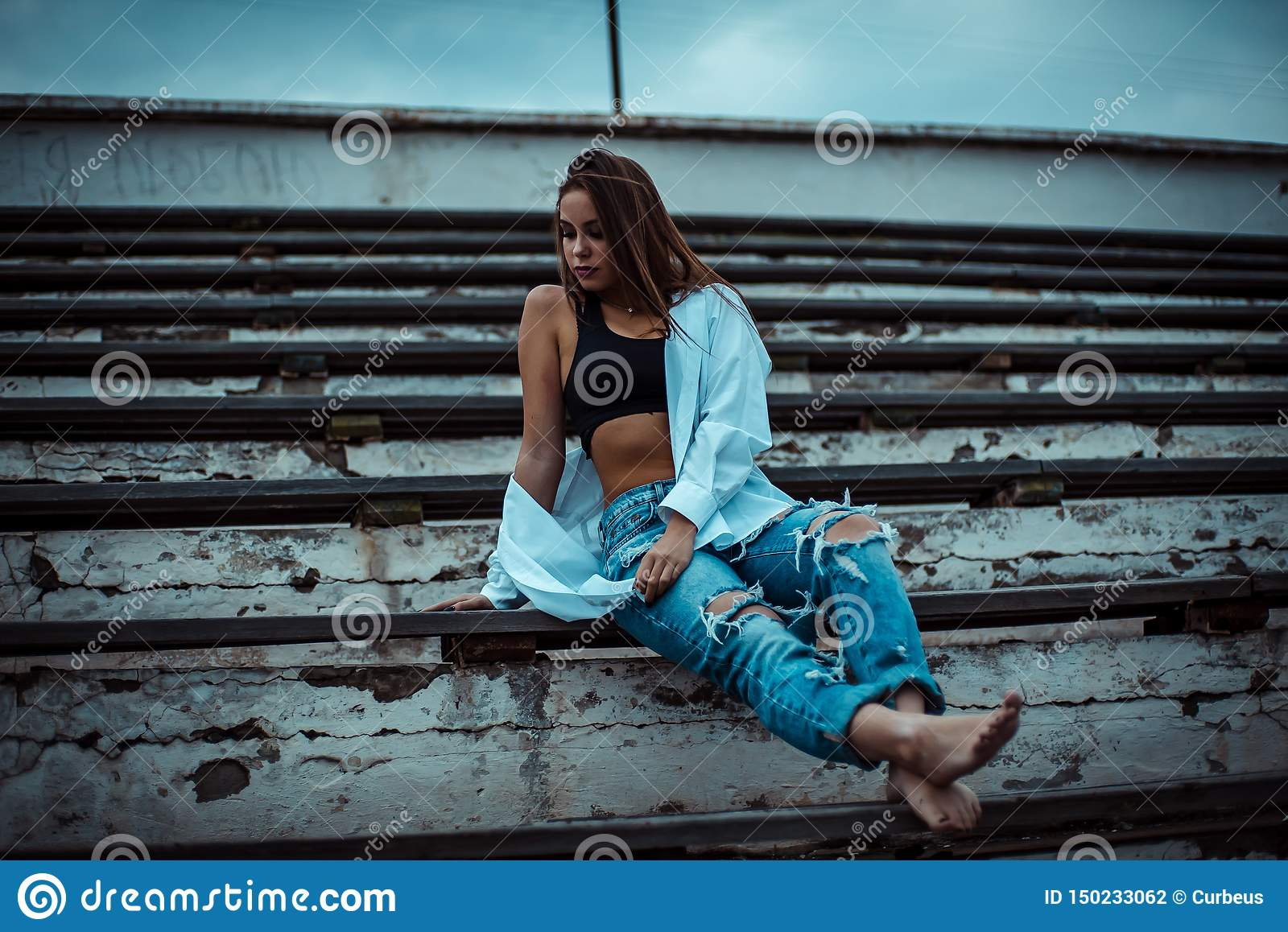 Woman sitting dreaming and relaxing. Sunset. Summer. Outdoor