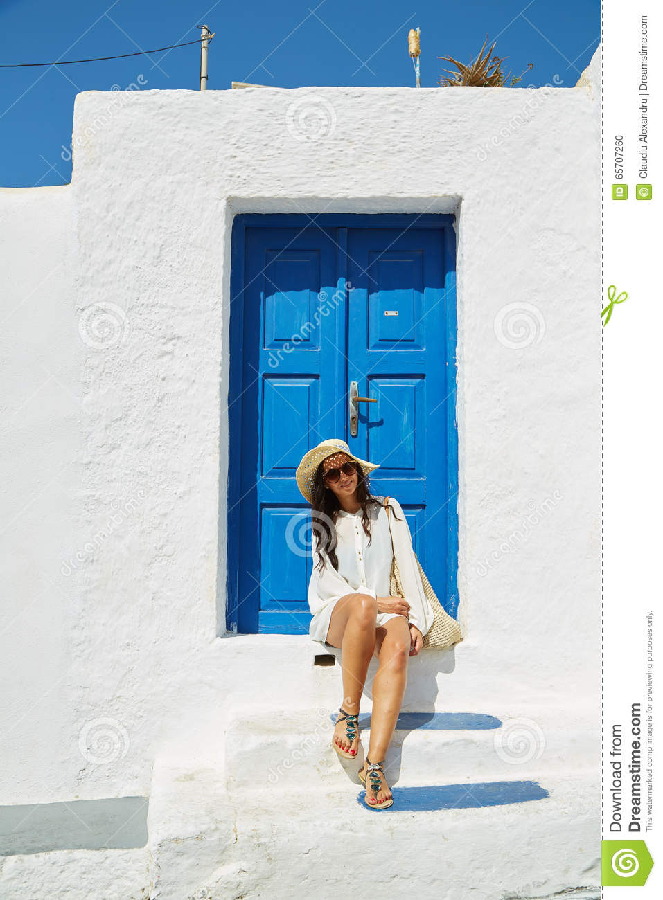 Download comp - Woman Sitting In Front Of A Blue Vintage Entrance Door Stock Photo