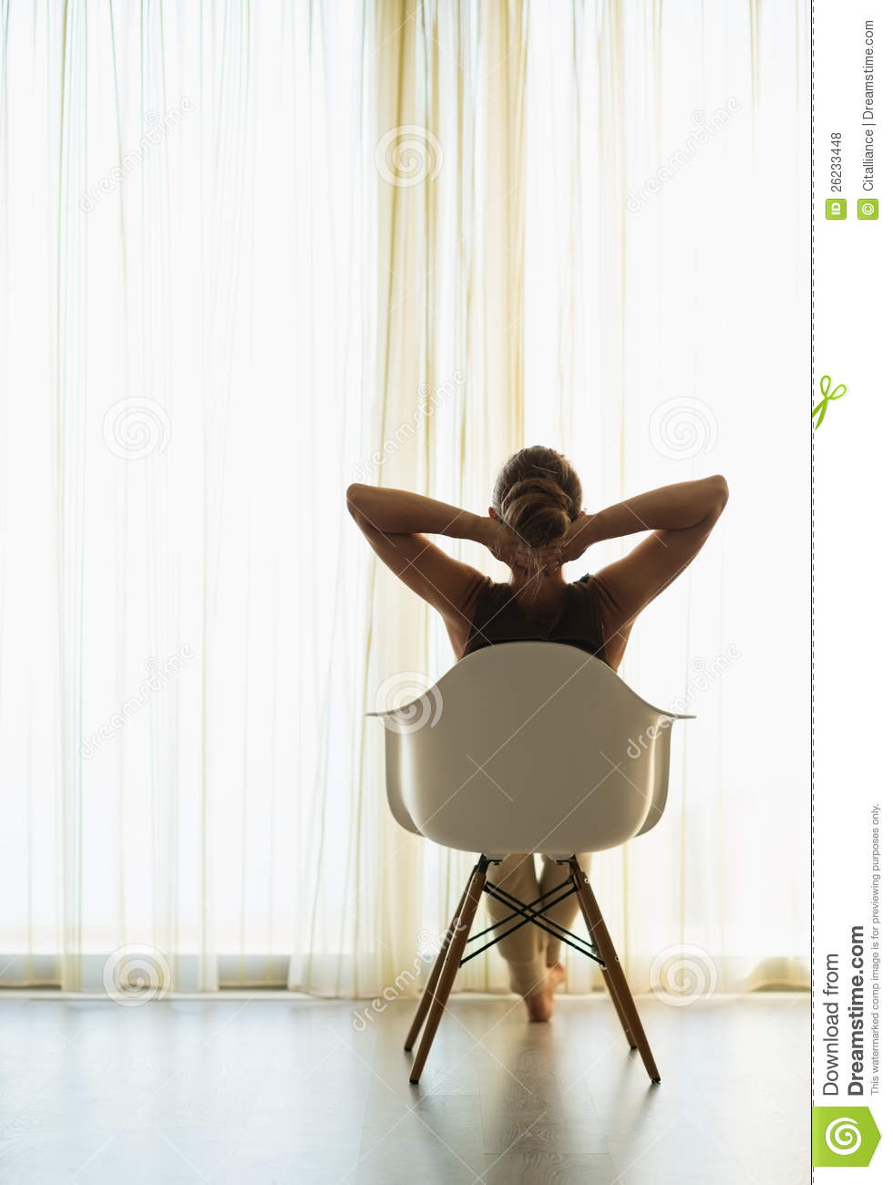 Woman Sitting In Front Of Window Rear View Stock Photo