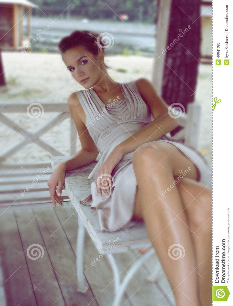 woman sitting in a gazebo wearing a beige silk dress stock image