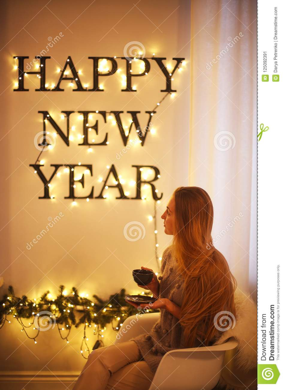 Woman sitting by the Happy New Year Holiday letters. Bright word
