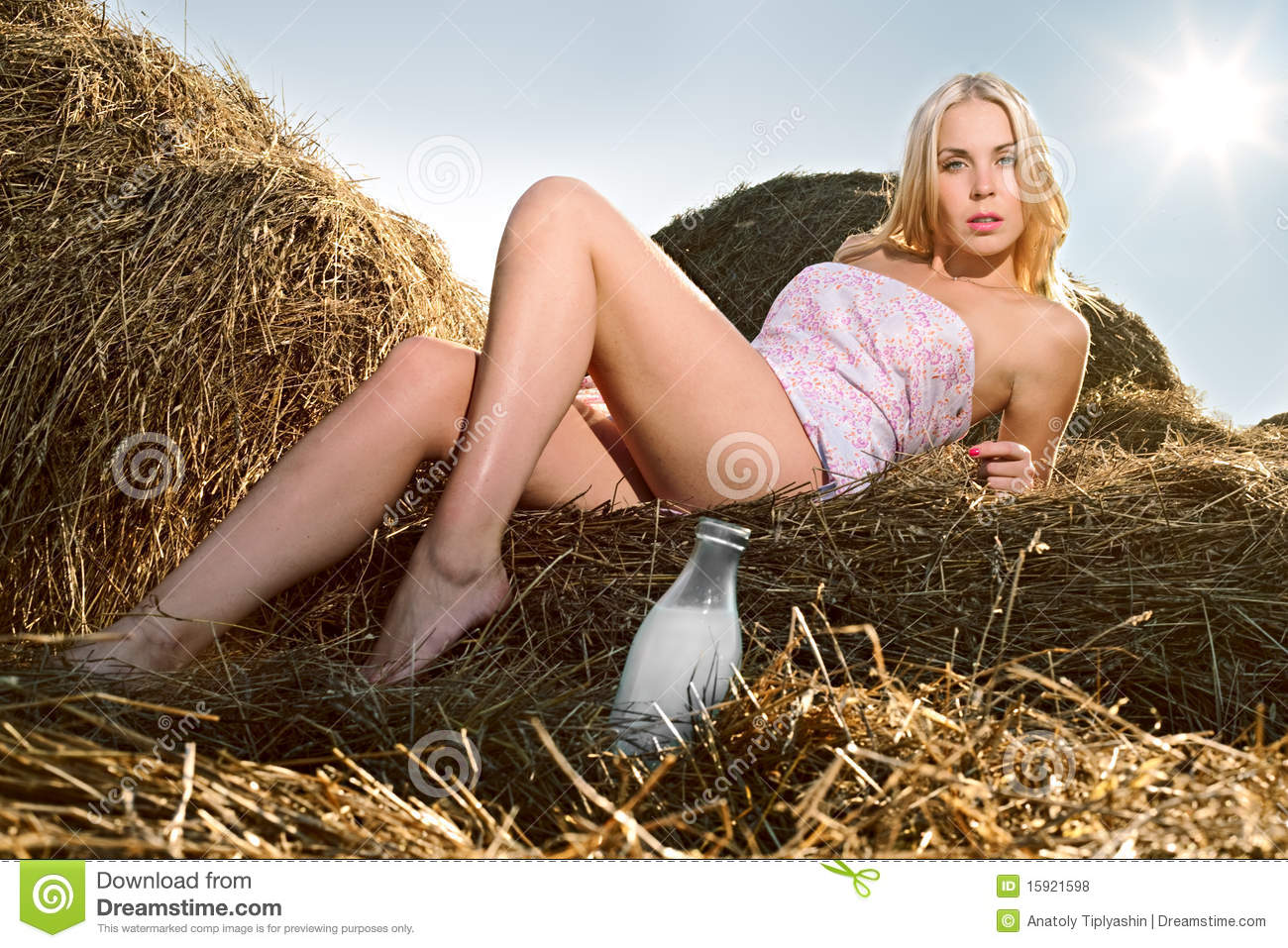 Woman sitting on the hay with a bottle of milk