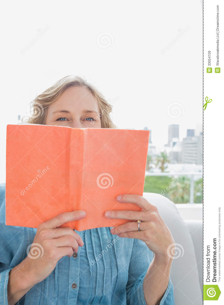 Book Covering Face : Woman sitting on her couch covering face with orange book