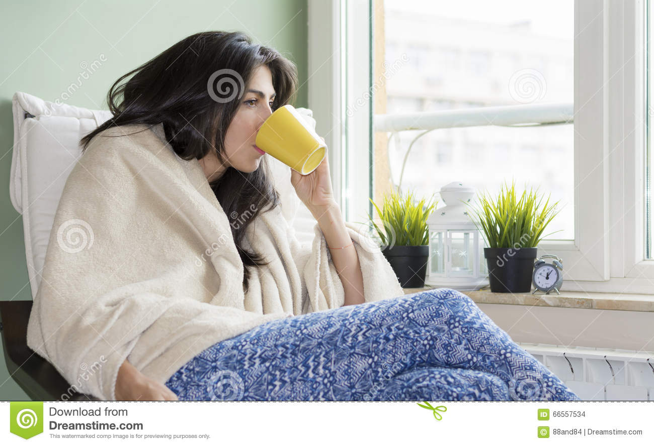 Woman sitting at home ,wrapped in a blanket ,drinking tea