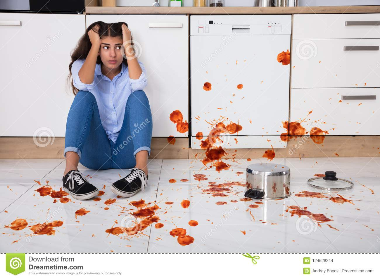 Woman Sitting On Kitchen Floor With Spilled Food