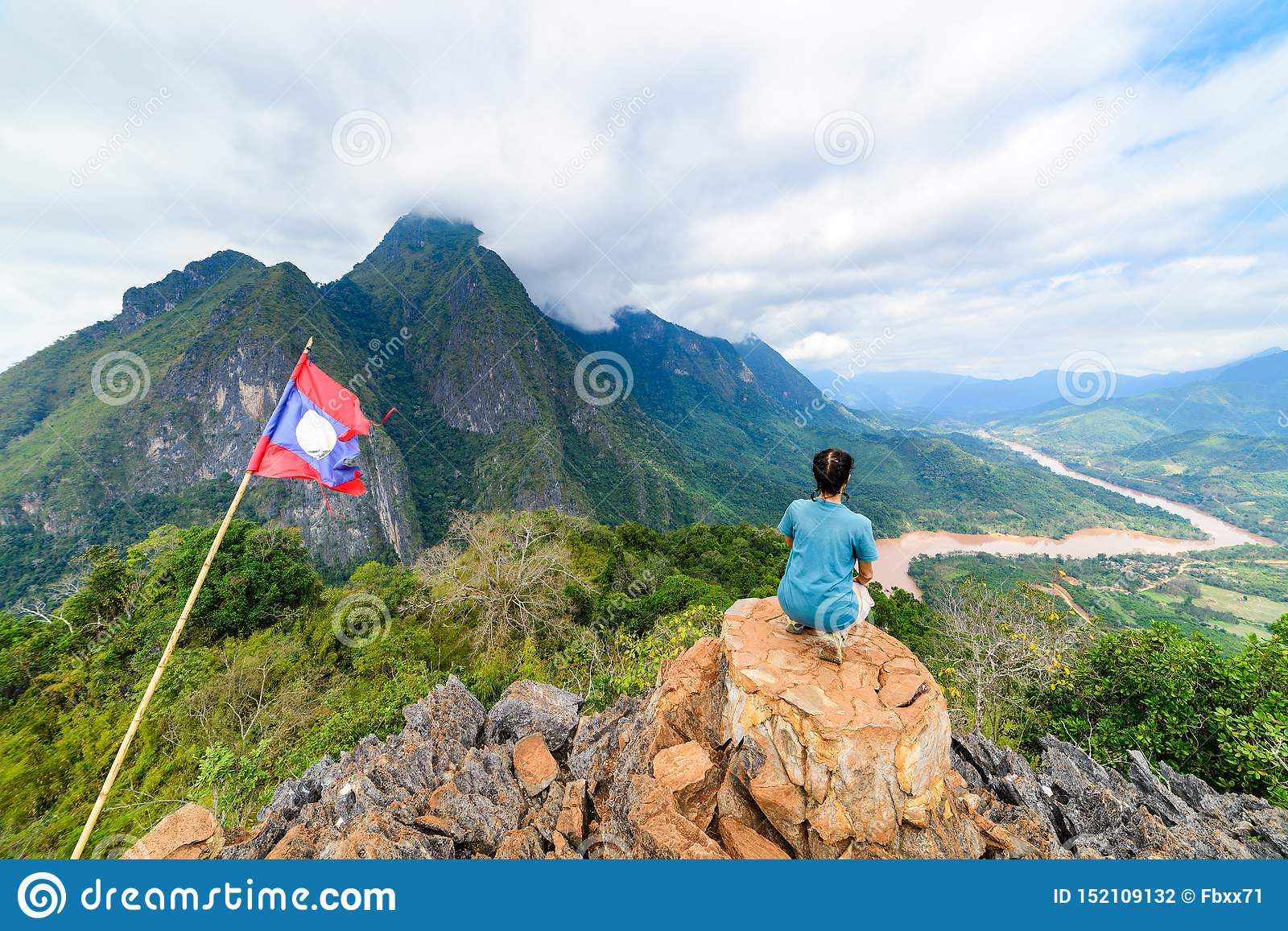 Woman sitting on mountain top at Nong Khiaw Nam Ou River valley Laos mature people traveling millenials concept travel destination