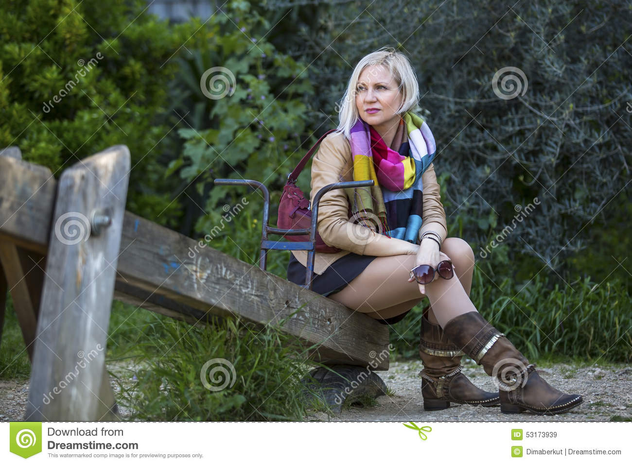 Woman Sitting On An Old Wooden Swing At The Park Stock