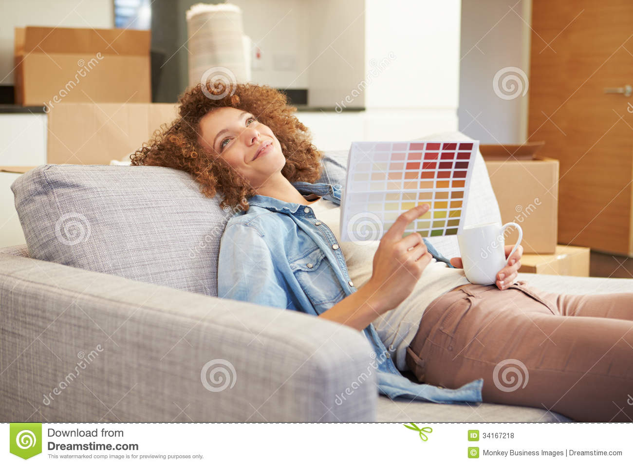 Hot Paint woman sitting on sofa looking at paint charts royalty free stock