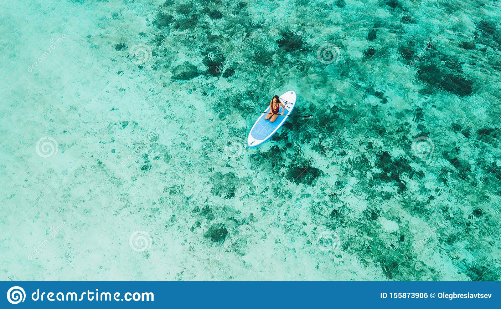 Woman sitting on sup board and enjoying coral reef