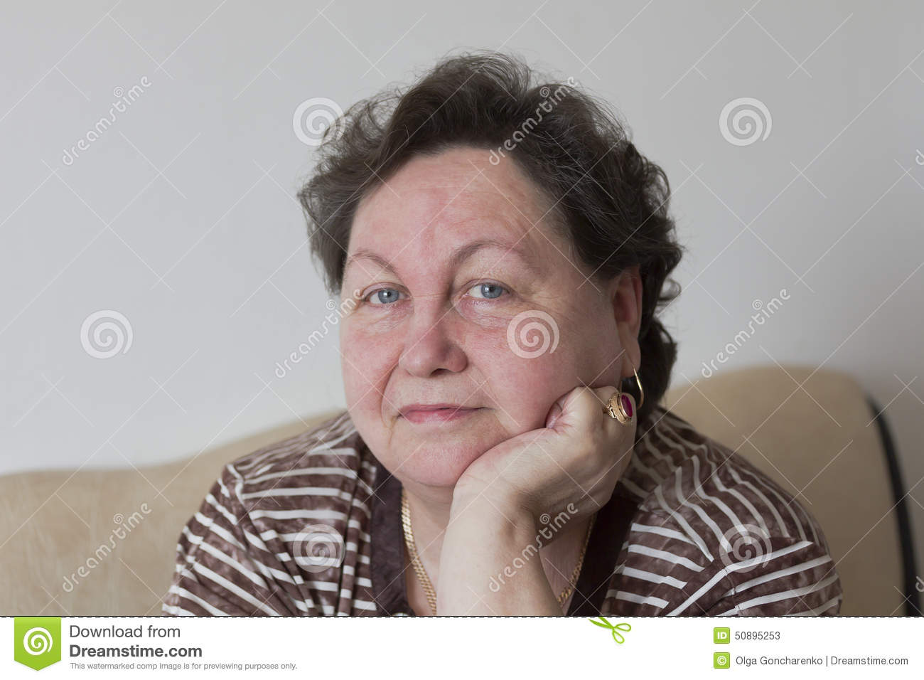 Woman Sitting At The Table Leaning On One Arm Stock Photo