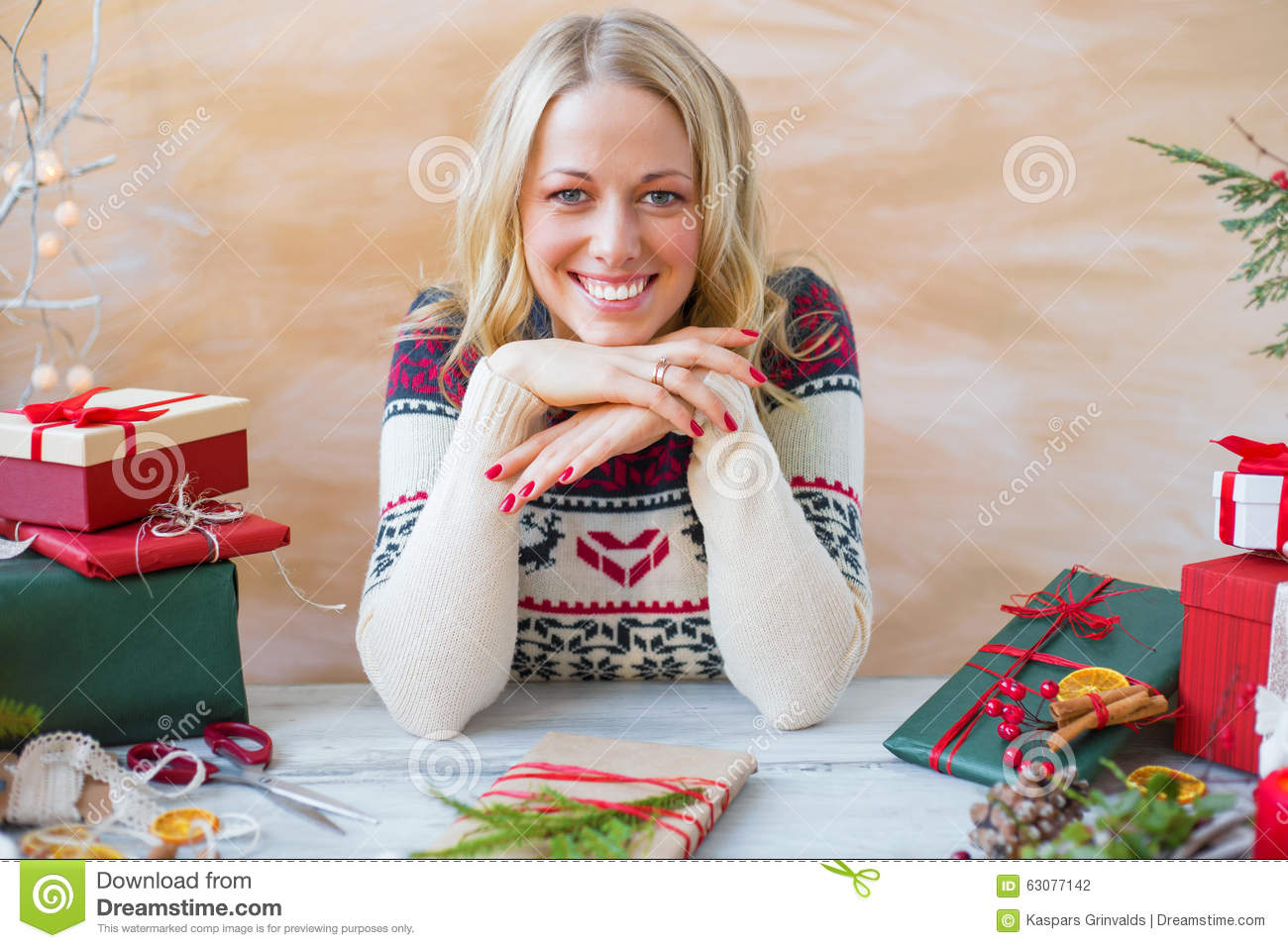 Woman sitting by the table and preparing gifts for - Table gifts for christmas ...