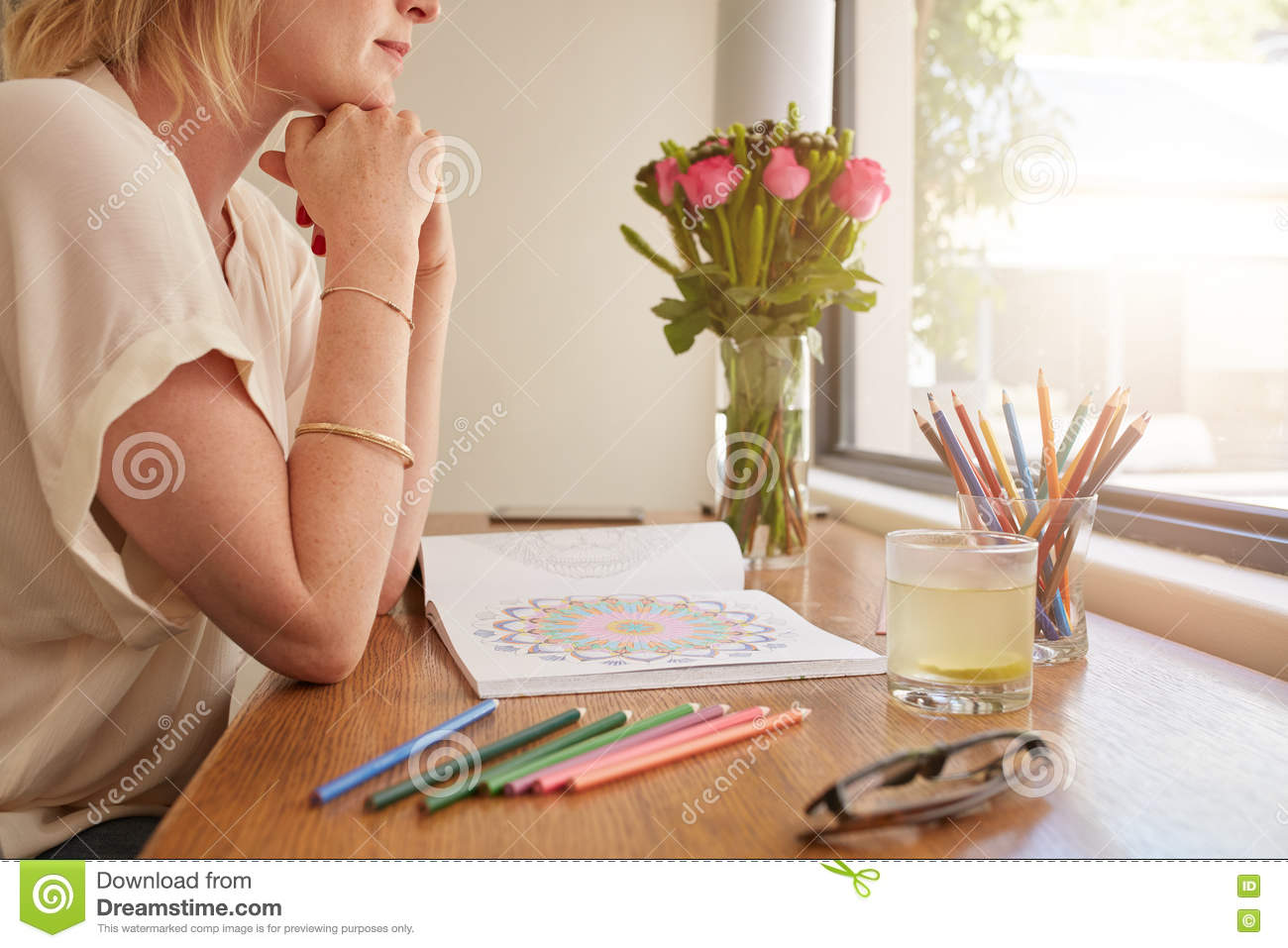 Woman sitting at a table and thinking with adult coloring book