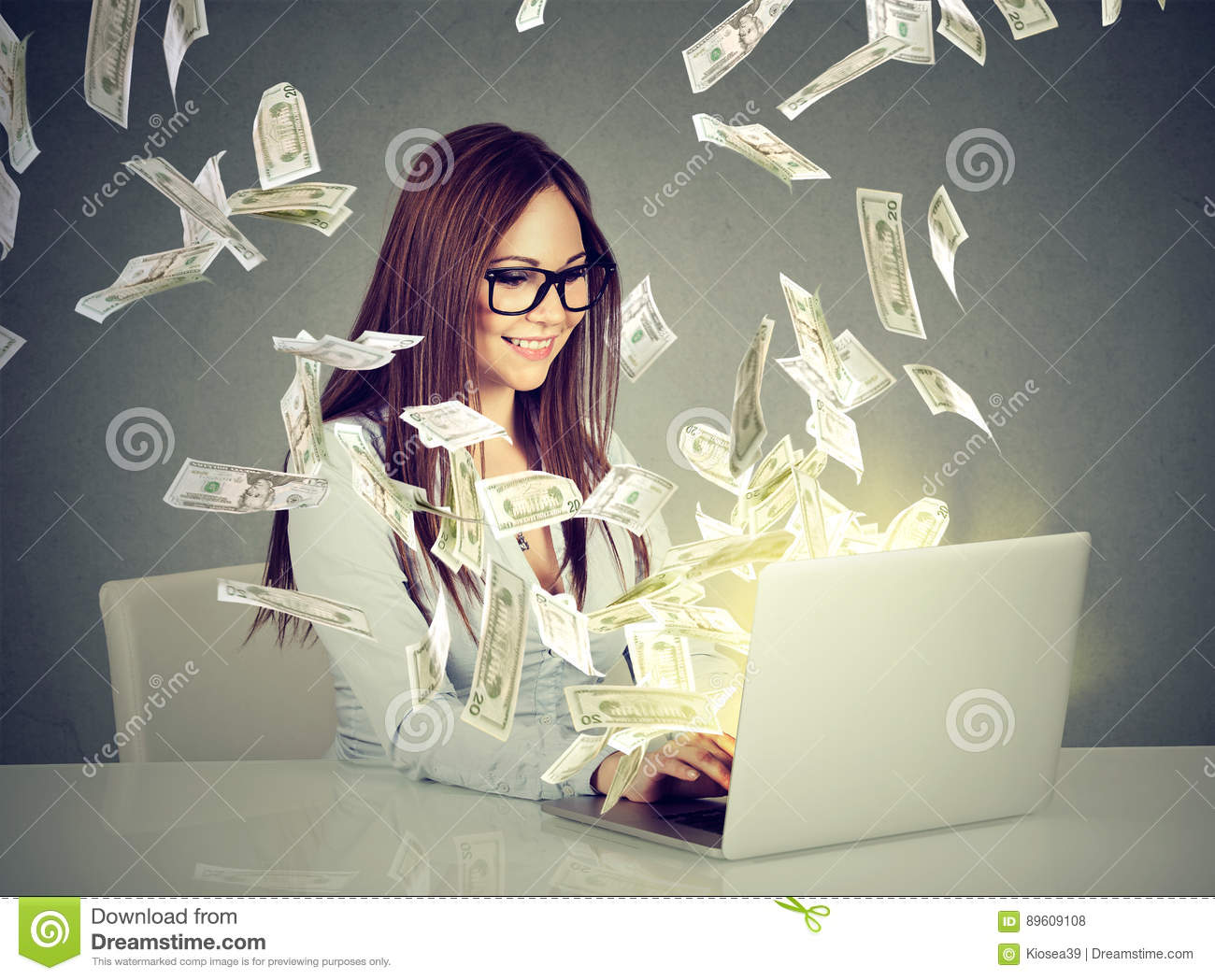 Woman sitting at table using working on a laptop computer making money