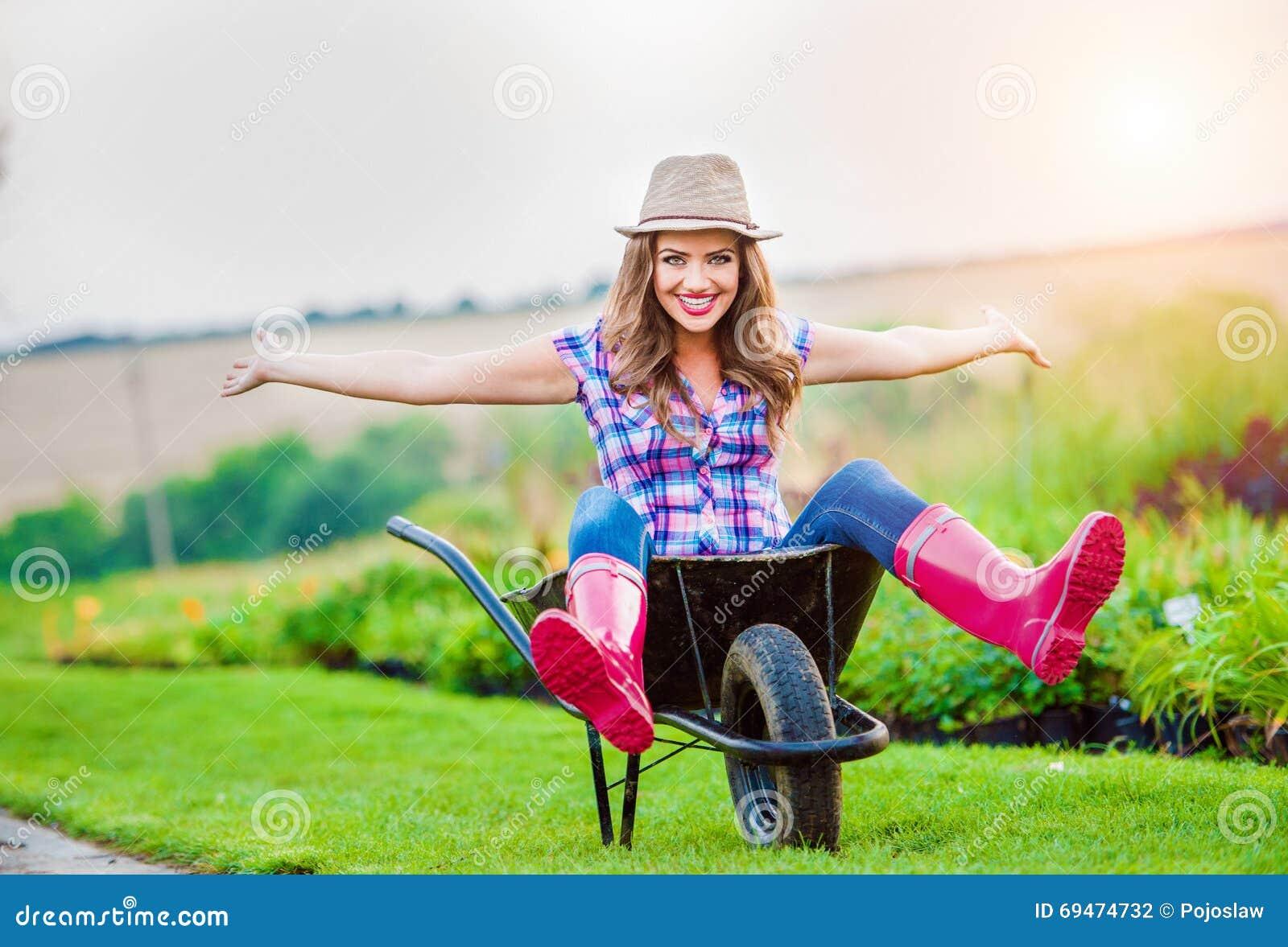 Woman Sitting In Wheelbarrow In Sunny Green Garden Stock ...
