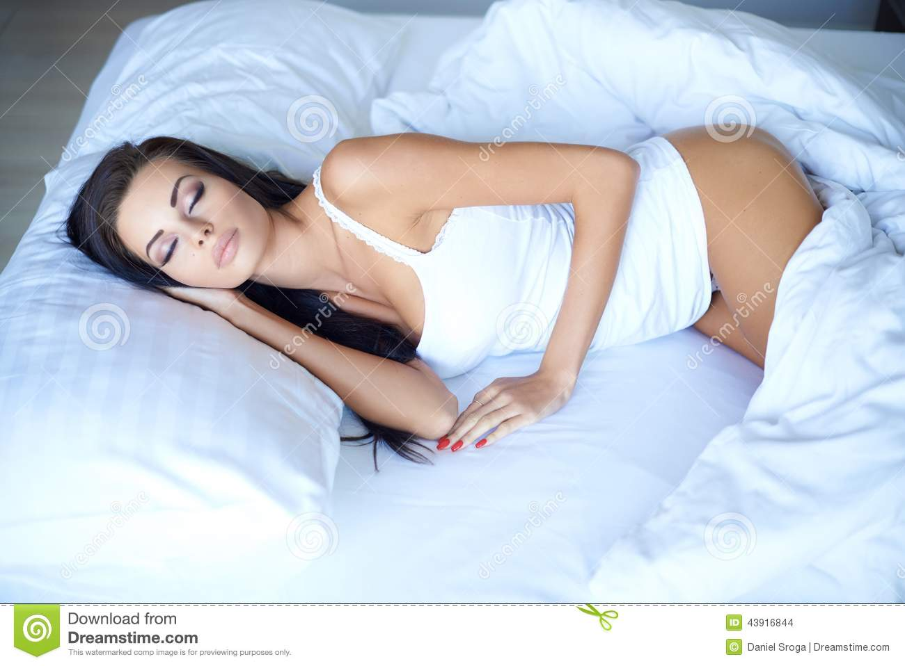 Beautiful young woman sleeping peacefully in bed on a hot night with the  white duvet down around her knees and her body in sleepwear uncovered cf79585d5