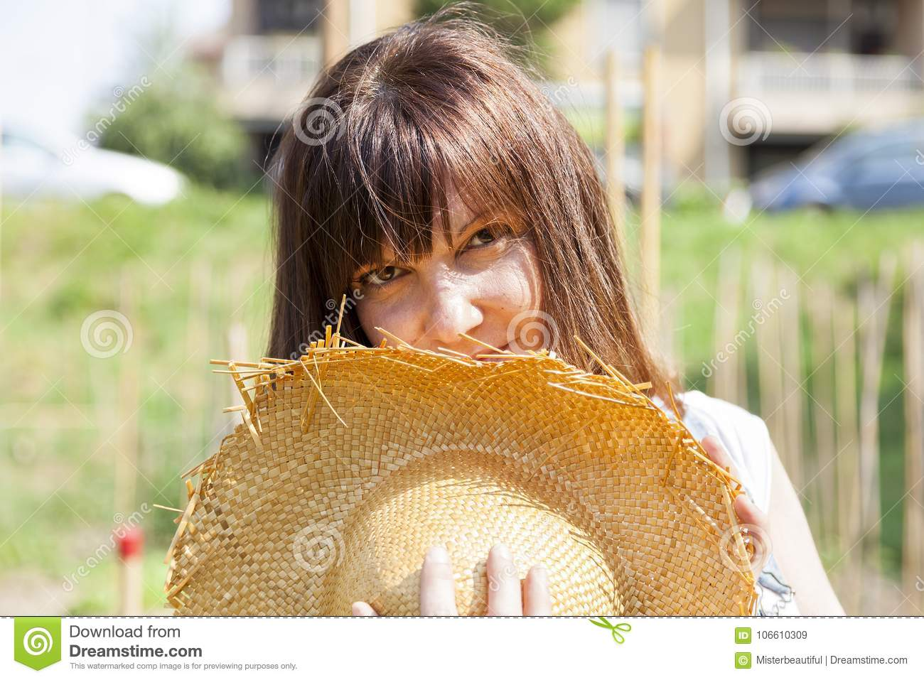 Woman smiling hidden behind a straw hat