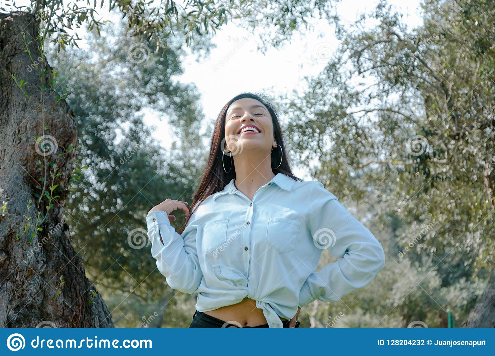 Woman smiling looking up to blue sky taking deep breath celebrating freedom. Positive human emotion face expression