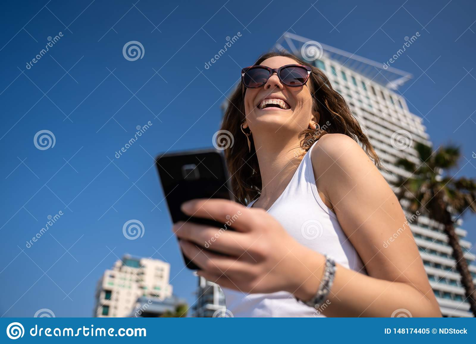 Young woman using the phone. City Skyline In Background