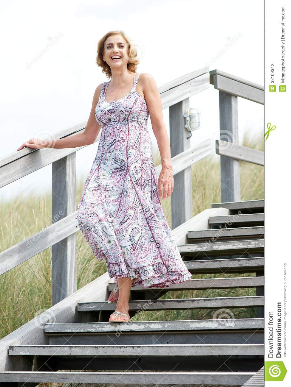Woman Smiling And Walking Downstairs Outdoors Stock