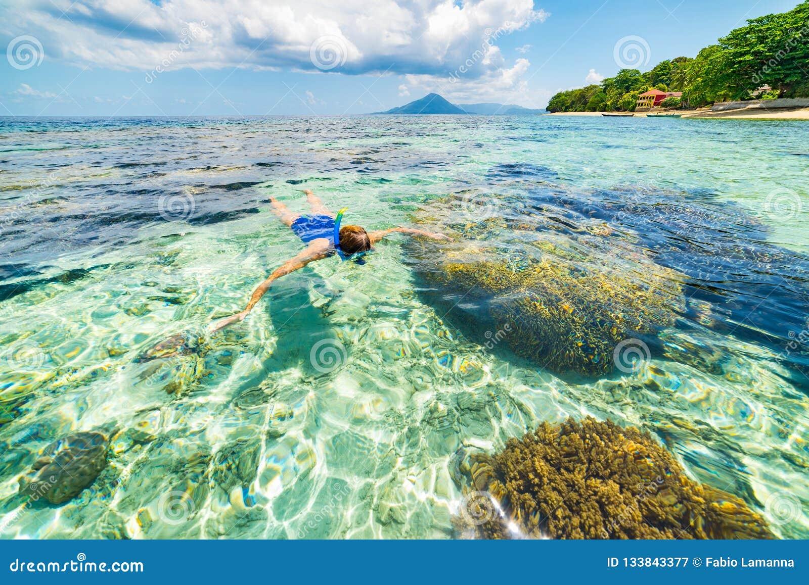Woman snorkeling on coral reef tropical caribbean sea, turquoise blue water. Indonesia Banda archipelago, Moluccas Maluku, tourist