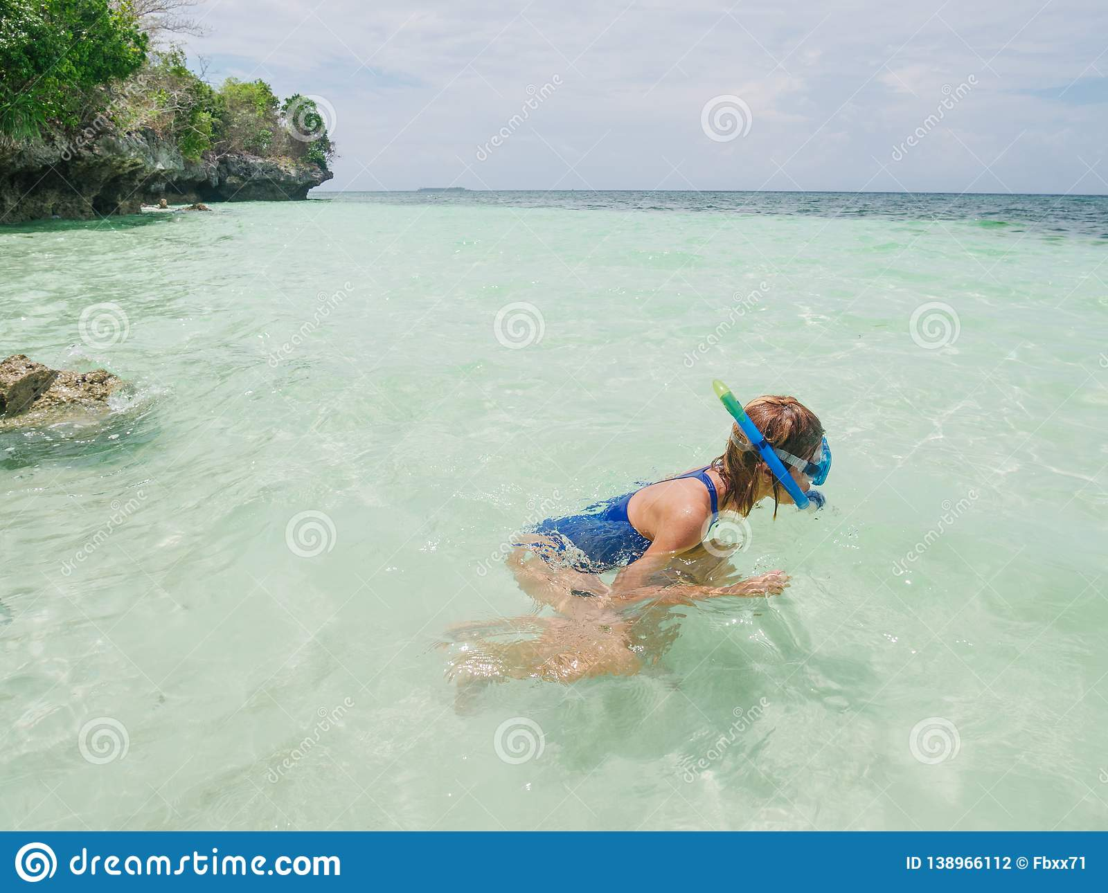 Woman snorkeling on coral reef tropical caribbean sea, turquoise blue water. Indonesia Banda archipelago, Moluccas Maluku, tourist