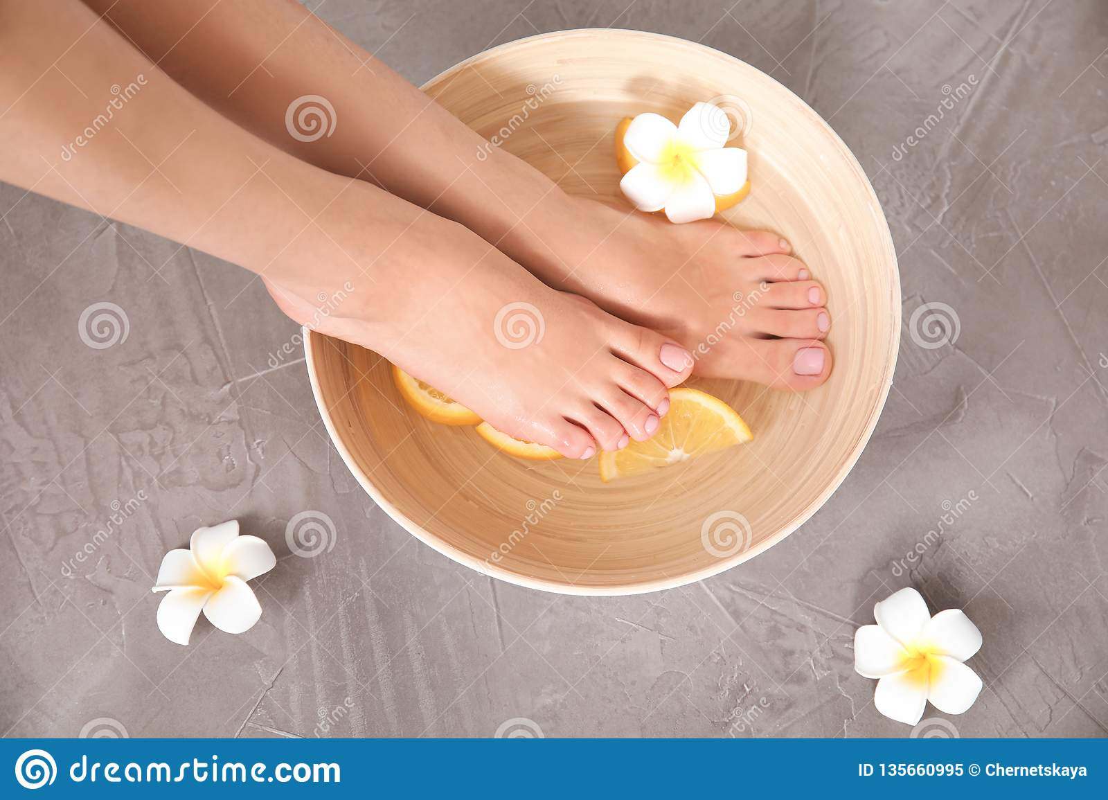 Woman soaking her feet in bowl with water, orange slices and flower on grey background, top view