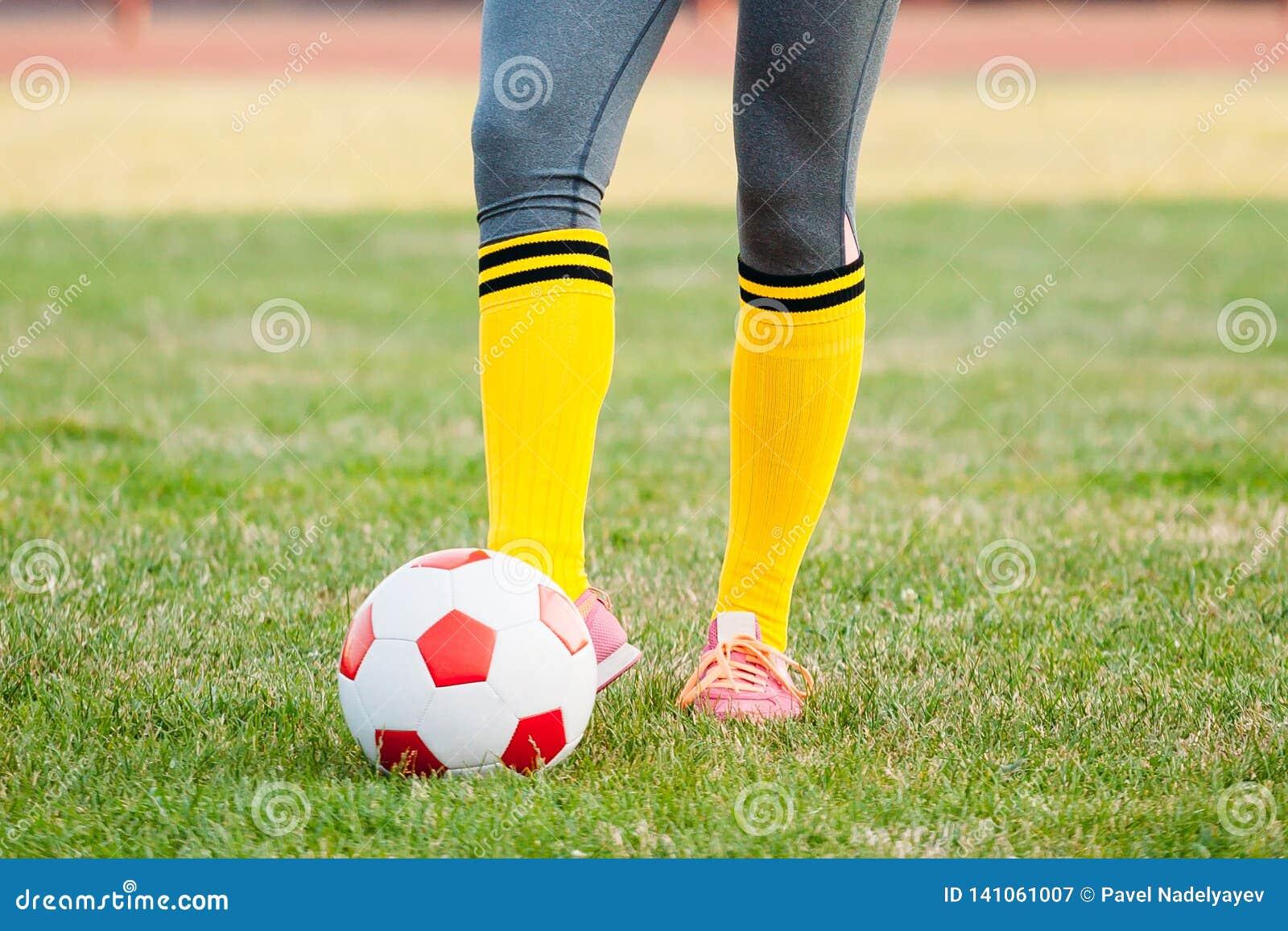 Young woman soccer player kicks ball on football field