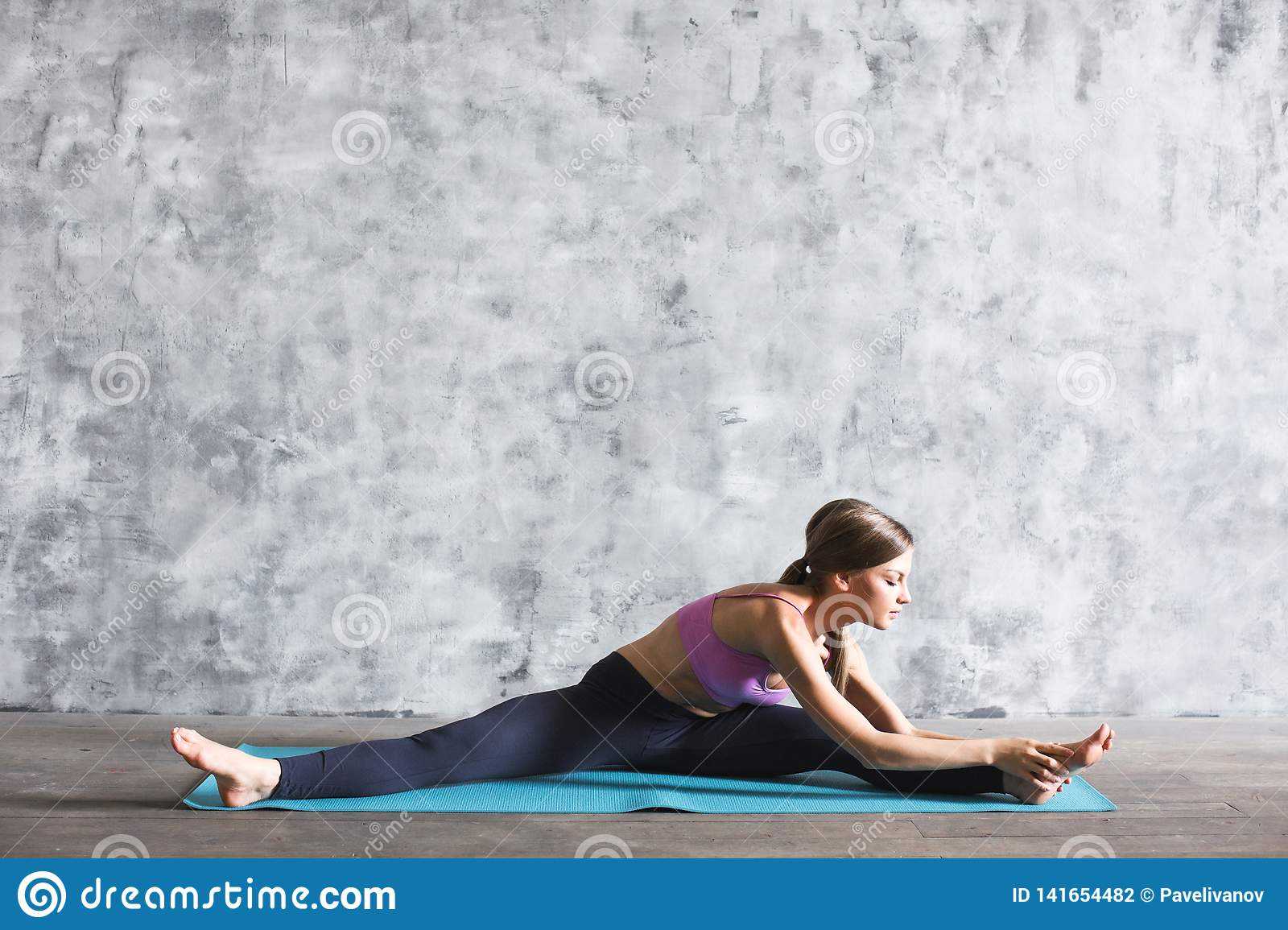 Woman in sportswear doing stretching exercises on a yoga mat in the gym