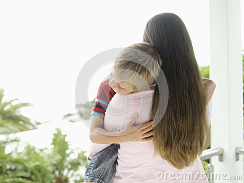Woman standing on balcony, carrying son (5-7), boy with eyes closed, rear view
