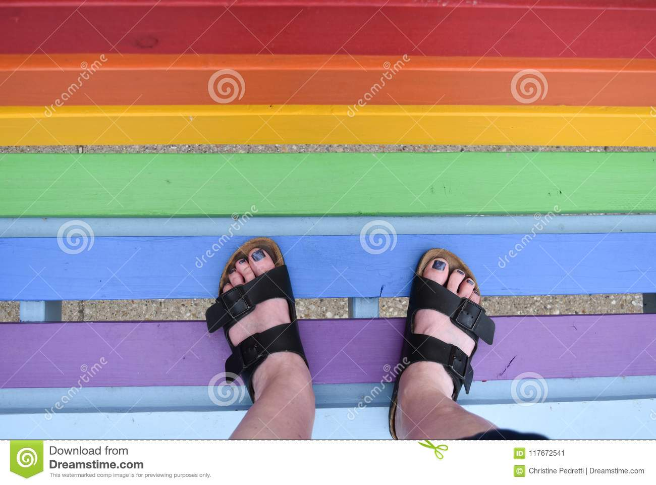 Woman standing on a bench painted in rainbow colors
