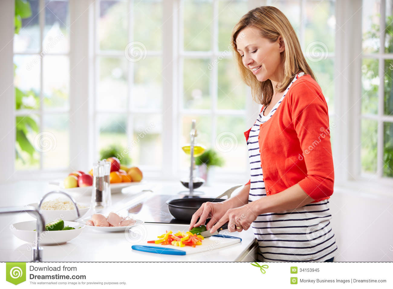 woman standing at counter preparing meal in kitchen stock image