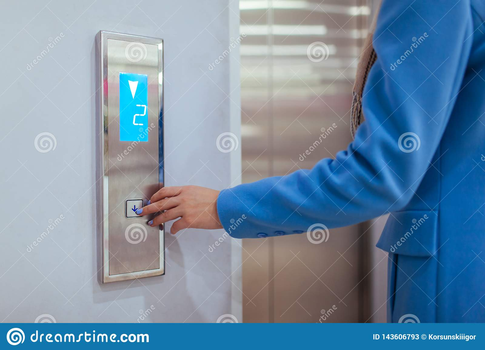 Woman Standing In Elevator And Pressing Button in shopping center