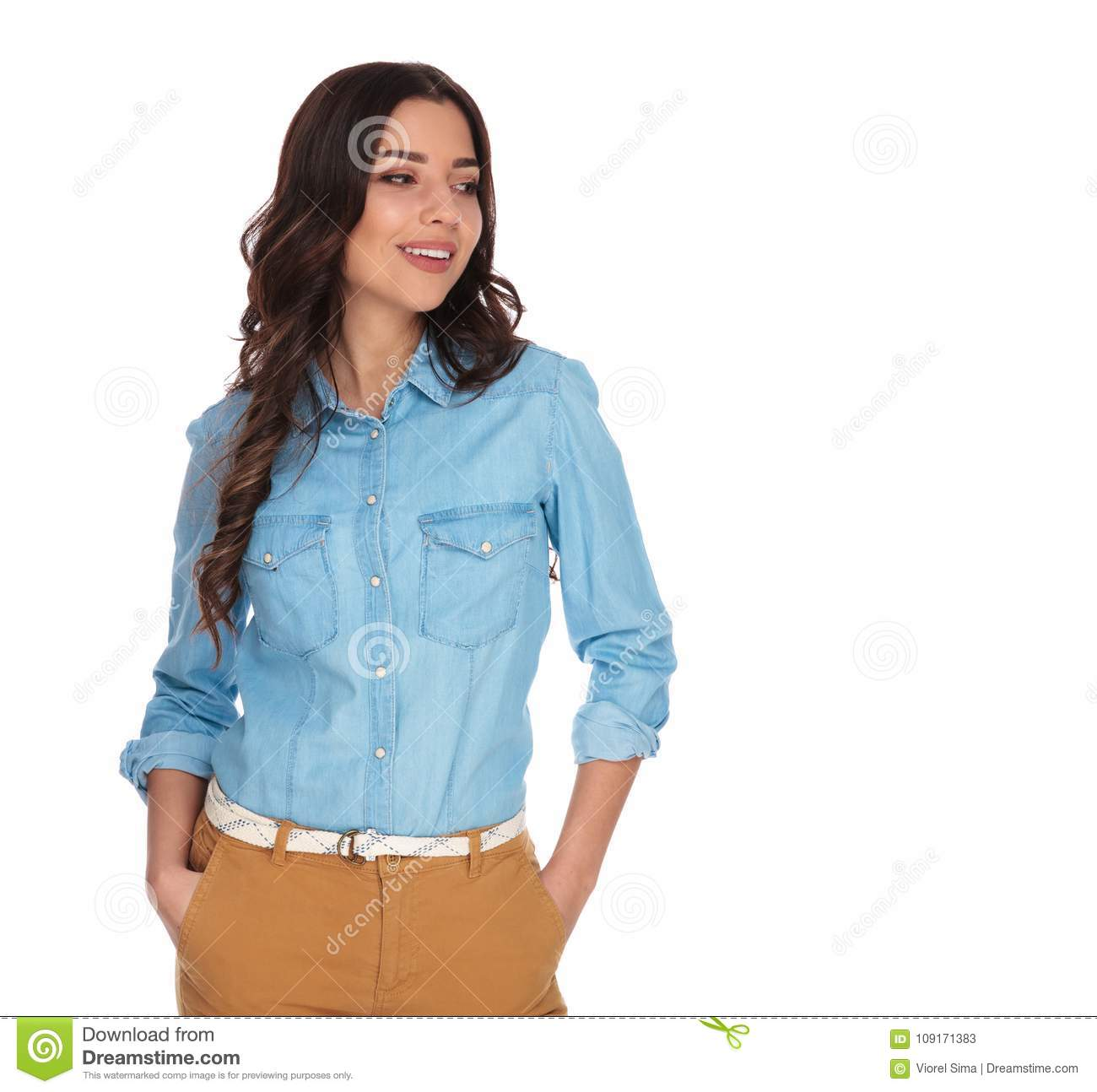 Woman Standing With Hands In Pockets Looks Away To Side