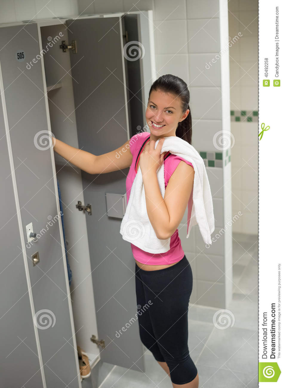 Woman standing by locker in changing room stock photo