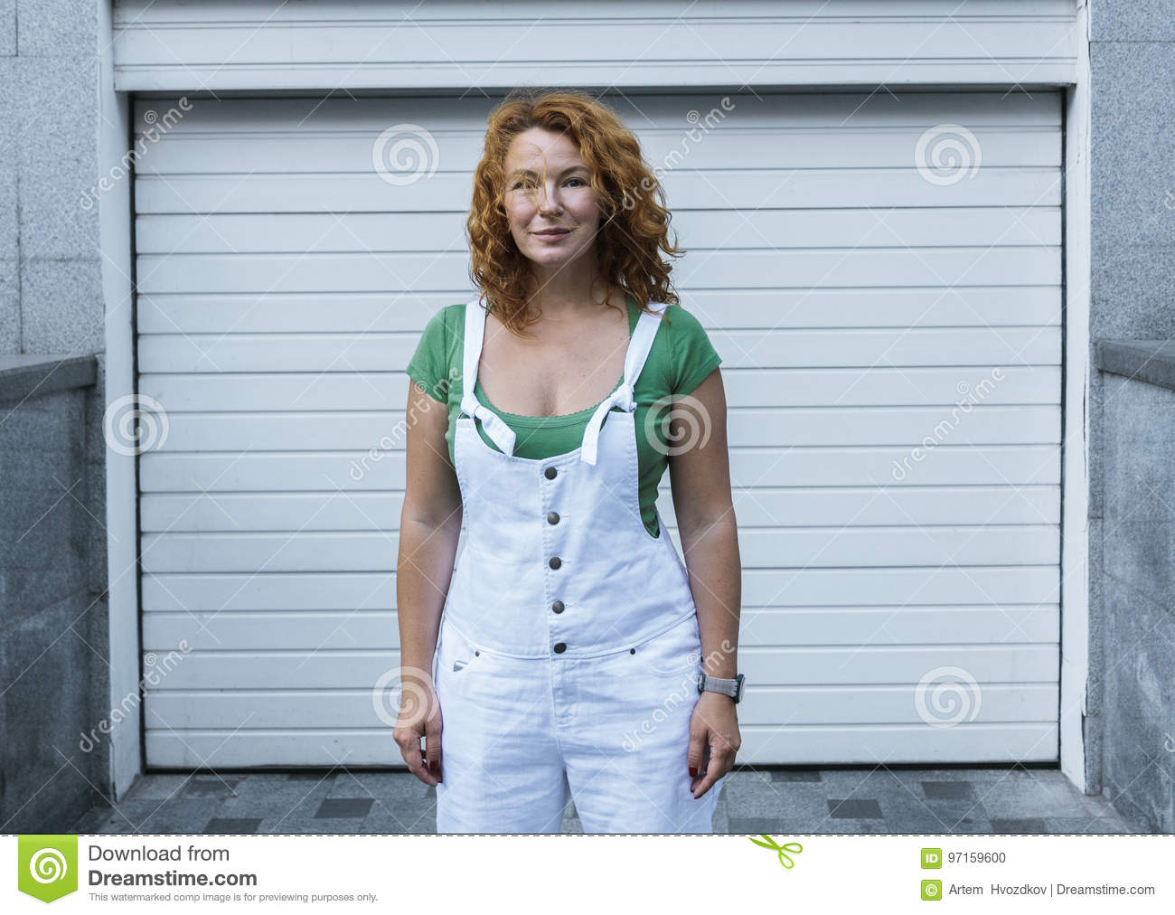 Woman standing on minimalism white pattern in white overalls. Day, outdoor