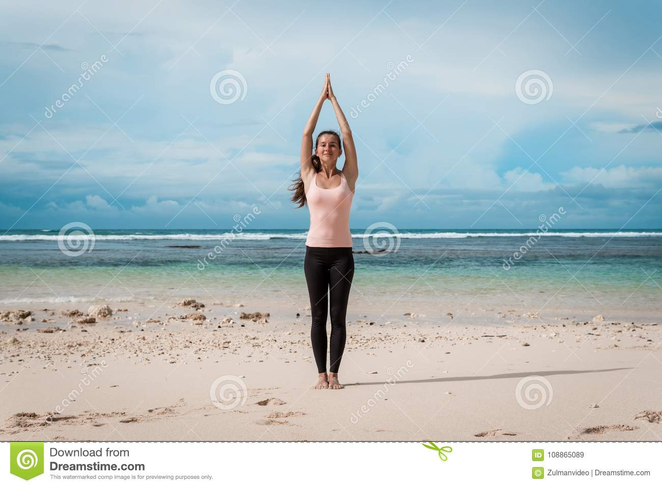 Woman Standing A Namaste Yoga Pose On The Beach Next To The Ocean Or