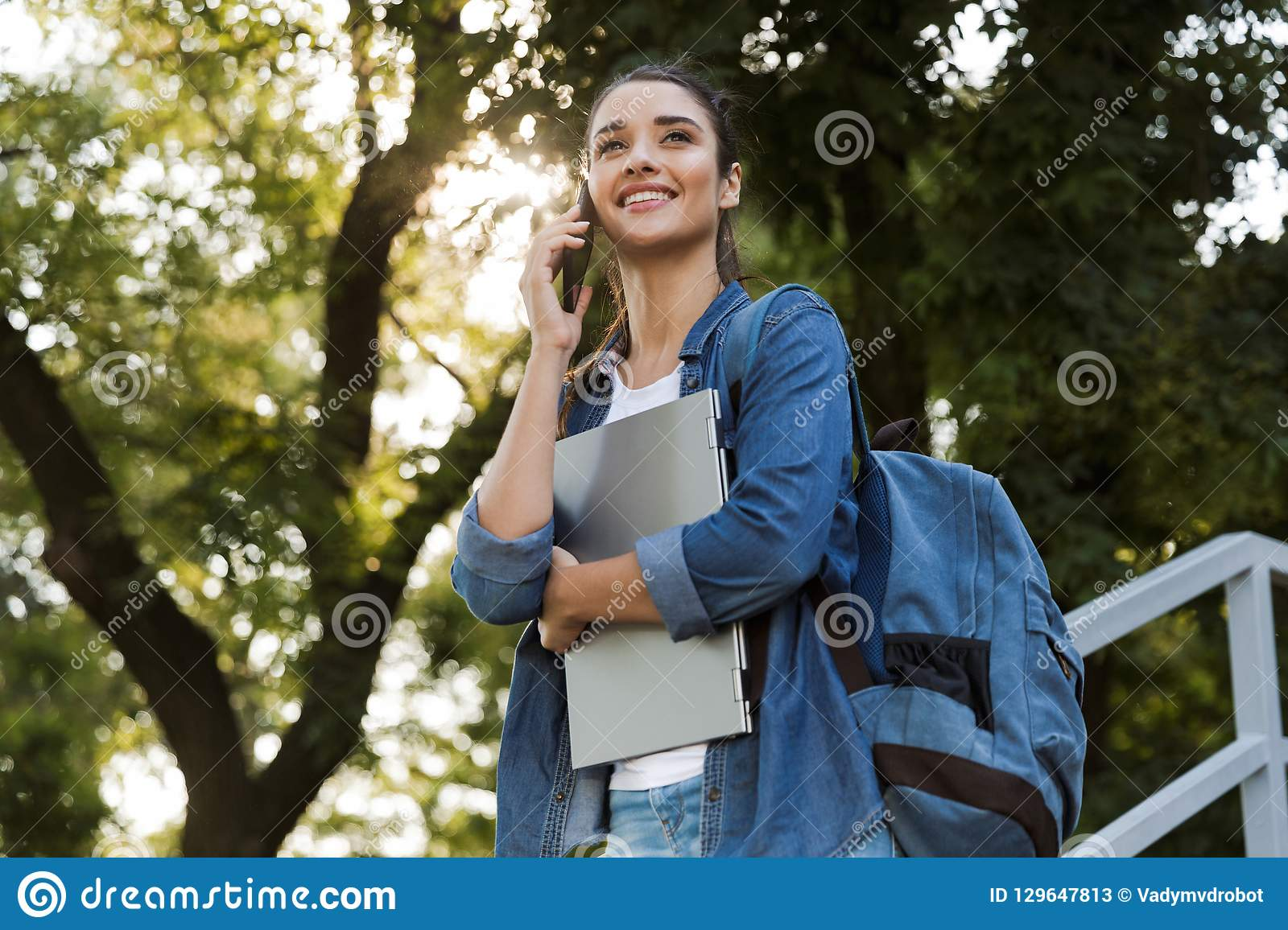 Woman standing outdoors holding laptop computer talking by mobile phone.