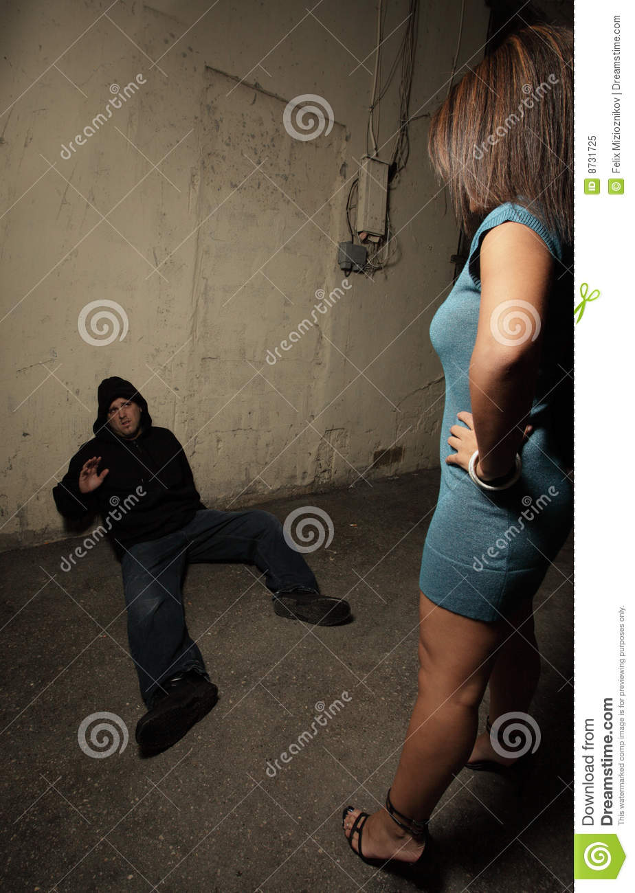 Woman standing over the robber who she just assaulted while the man is ...