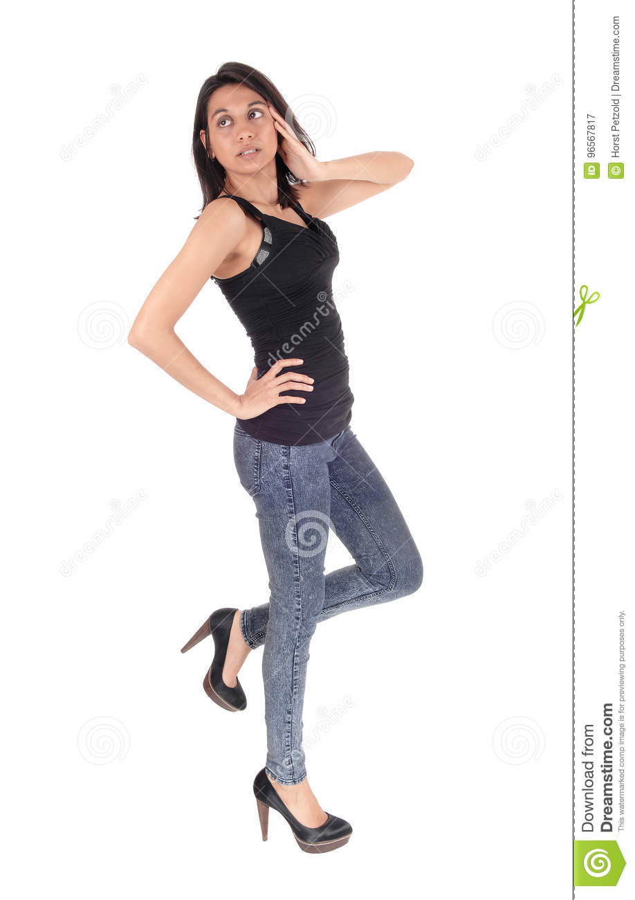 65155739ce A beautiful young Hispanic woman standing in profile in a black t-shirt and  jeans