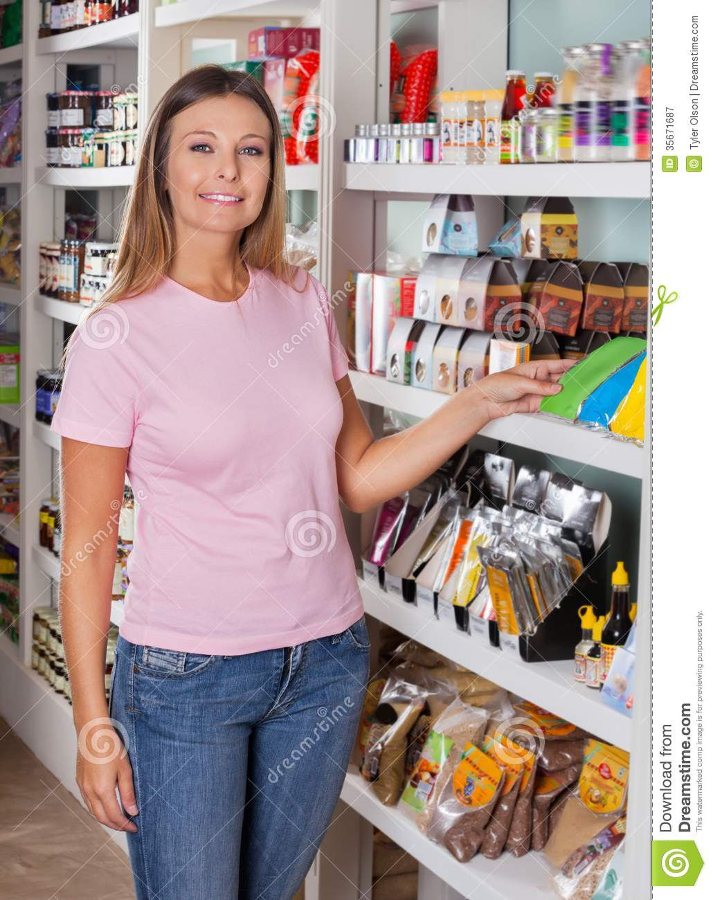of beautiful mid adult woman standing by shelf in grocery store