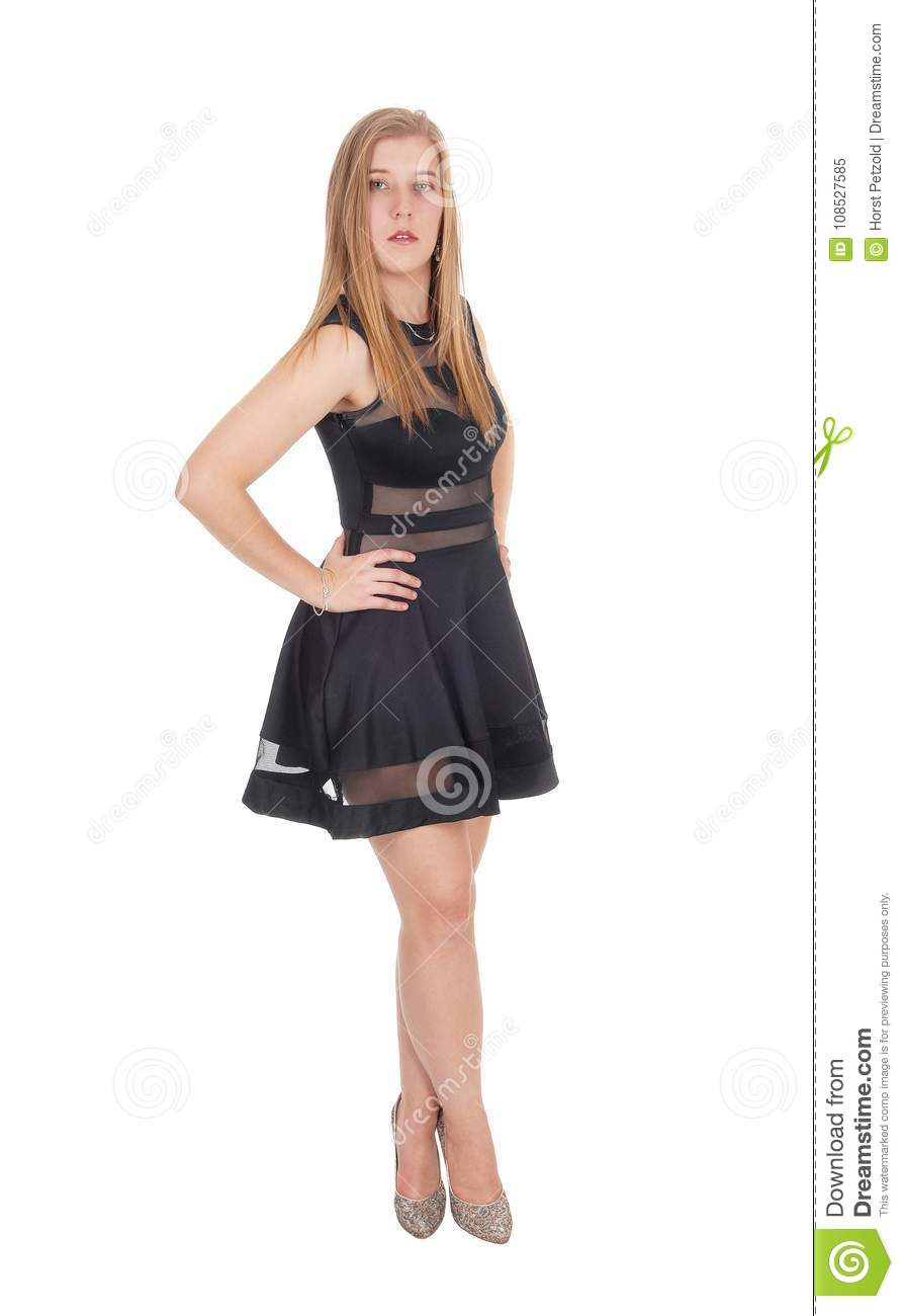 a95609b3b5864 A beautiful young woman standing in a short black dress and high heels, at  the camera, isolated for white background