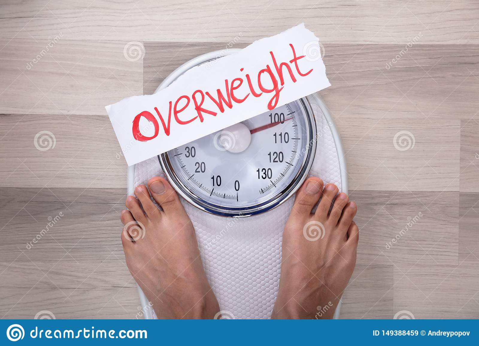 Woman Standing On Weighing Scales Low Section Stock Photo