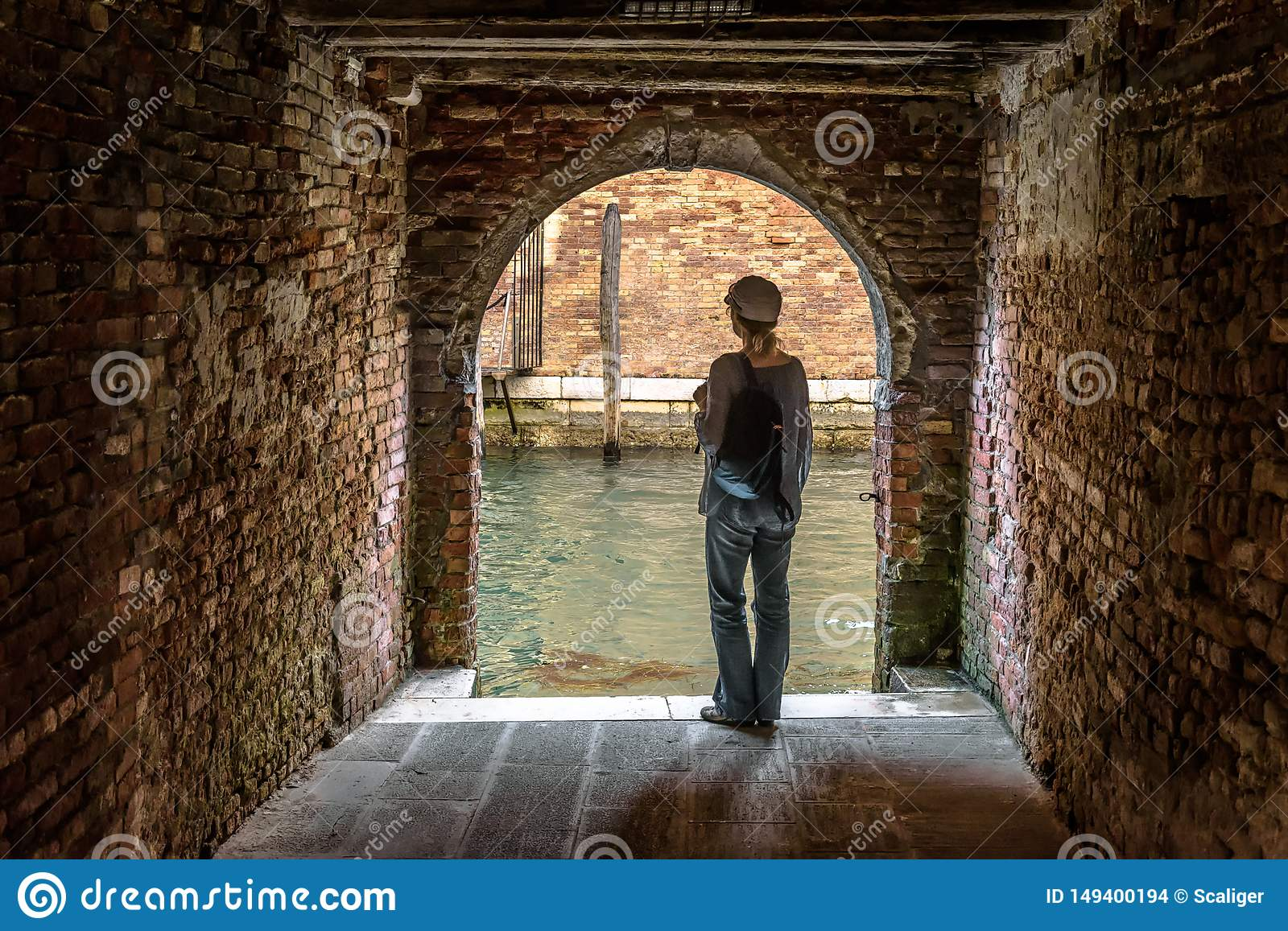 Woman Stands At Exit To Canal From Courtyard Venice Italy Stock