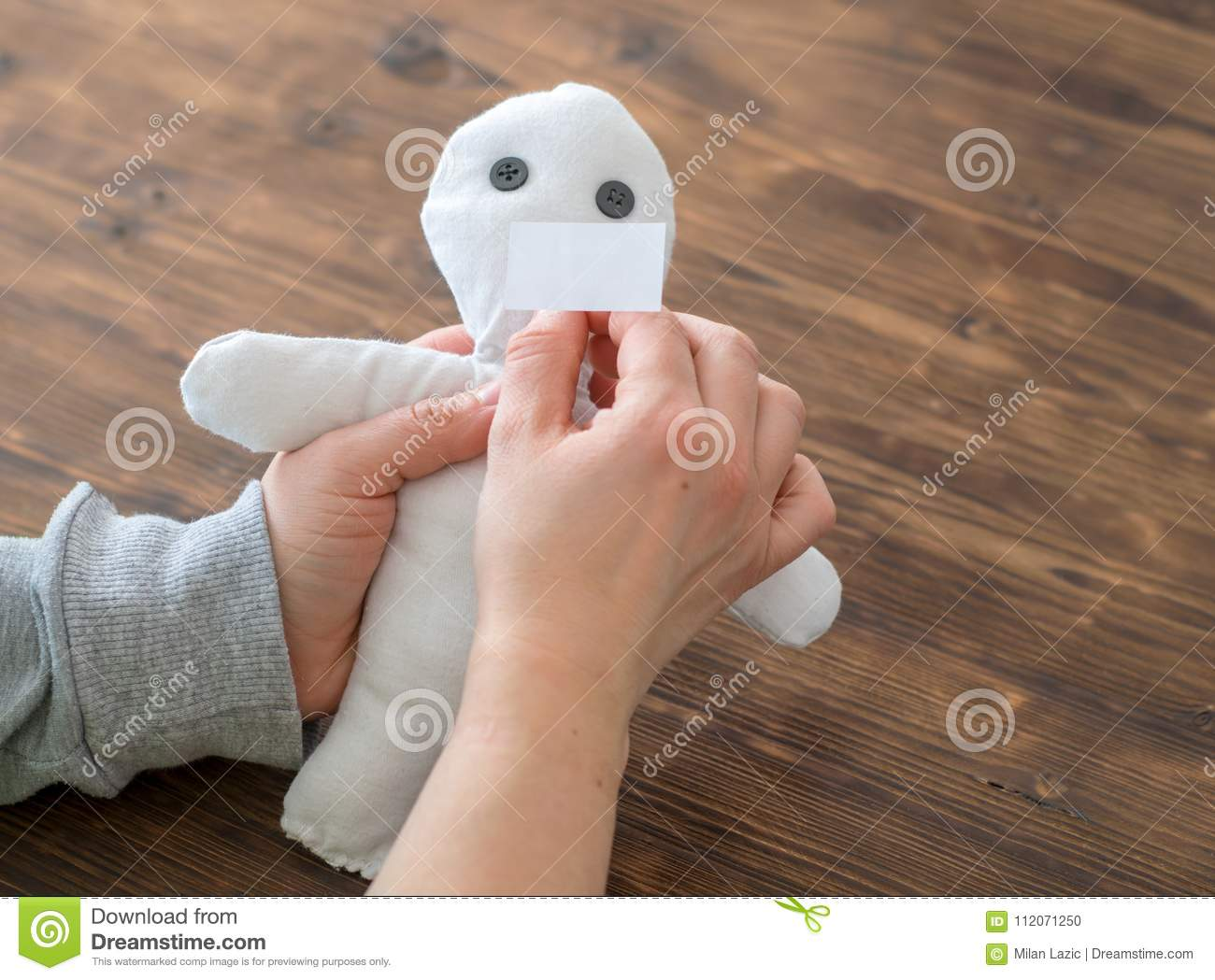 Woman Sticking A Needle Into A Voodoo Doll Stock Photo