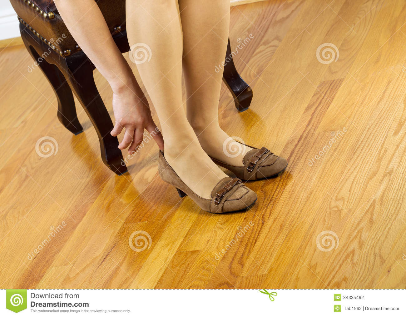 Woman In Stockings Putting On Shoes Stock Photo